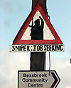 """An IRA snipper sign displaying a new message """"SNIPPER - JOB SEEKING"""" hangs on a telegraph pole 4miles outside Crossmaglen, South Armagh, Belfast, Sunday April 12, 1998.During a easter message the IRA said that the will study the Stormont Document and have praised the efforts of Sinn fein leadership. (AP Photo/Paul McErlane)"""
