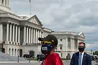 "Michael Wheeler, of Kansas City, MO, (left) wears his ""Super Jesus"" outfit and face mask while a US Capitol Security detail stands at right as House Minority Leader Rep. Kevin McCarthy (R-Calif.) holds a media availability with House Minority Whip Rep. Steve Scalise (R-LA), House GOP Conference Chairwoman Liz Cheney (R-WY) and others, to announce that Republican leaders have filed a lawsuit against House Speaker Nancy Pelosi and congressional officials in an effort to block the House of Representatives from using a proxy voting system to allow for remote voting during the coronavirus pandemic, outside of the U.S. Capitol in Washington, DC., Wednesday, May 27, 2020. Credit: Rod Lamkey / CNP/AdMedia"