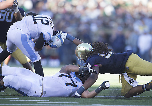October 11, 2014:  Notre Dame defensive line Sheldon Day (91) grabs the helmet of North Carolina quarterback Marquise Williams (12) during NCAA Football game action between the Notre Dame Fighting Irish and the North Carolina Tar Heels at Notre Dame Stadium in South Bend, Indiana. Notre Dame defeated North Carolina 50-43