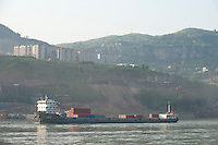 Daytime landscape view of river container ship on the Cháng Jiāng with commercial buildings in the background in the Wànzhōu District in the Chongqing Municipality.  © LAN