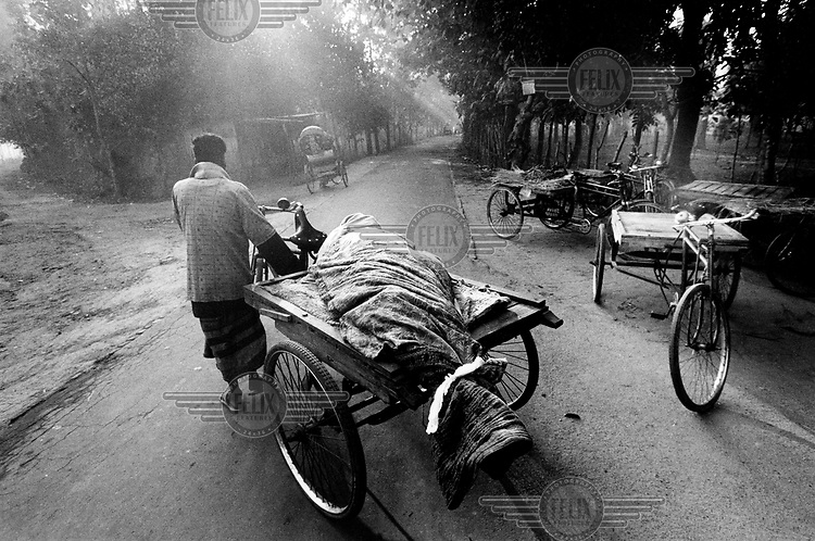 A critically ill man was brought to hospital by his wife and daughter, but he died shortly after being admitted. A rickshaw driver carries away the dead body.