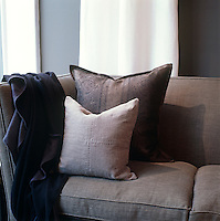 In the living room the plain brown linen sofa is enlivened with a paisley-print cushion and a grey woollen throw