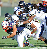 30 October 2010:  FIU cornerback Anthony Gaitor (7), linebacker Toronto Smith (13), and linebacker Aaron Davis (45) combine to tackle Florida Atlantic tight end Rob Housler (81) in the first quarter as the Florida Atlantic University Owls defeated the FIU Golden Panthers, 21-9, at Lockhart Stadium in Fort Lauderdale, Florida.