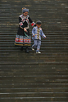 A woman of the ethnic Bouyei Tribe and her son walk down a staircase at Wangmo County in China's southwestern Guizhou Province, April 2019.