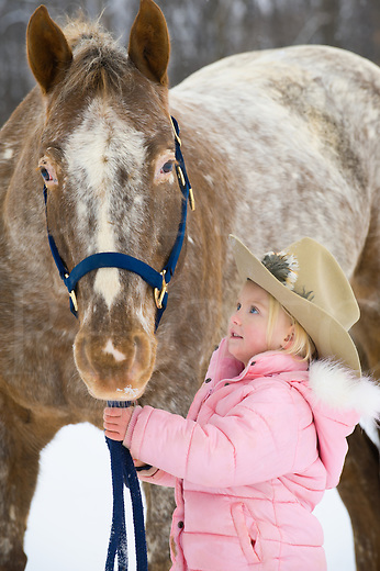 Little blonde girl holding big Appaloosa horse outdoors in snow, close up of preschooler wearing pink winter coat and cowby hat with animal, Pennsylvania, PA, USA.