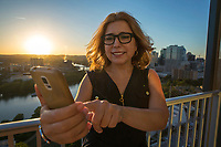 Attractive woman texting and taking selfie with smartphone over Austin Skyline background during bright sunny sunset - people, technology, Austin tourism and travel concept.