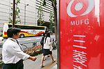 Pedestrians walk past a signboard of Bank of Tokyo-Mitsubishi UFJ on display outside its bank branch on May 17, 2017, Tokyo, Japan. Japan's biggest bank plans to shorten its name by dropping ''Tokyo'' to Bank of Mitsubishi UFJ. (Photo by Rodrigo Reyes Marin/AFLO)
