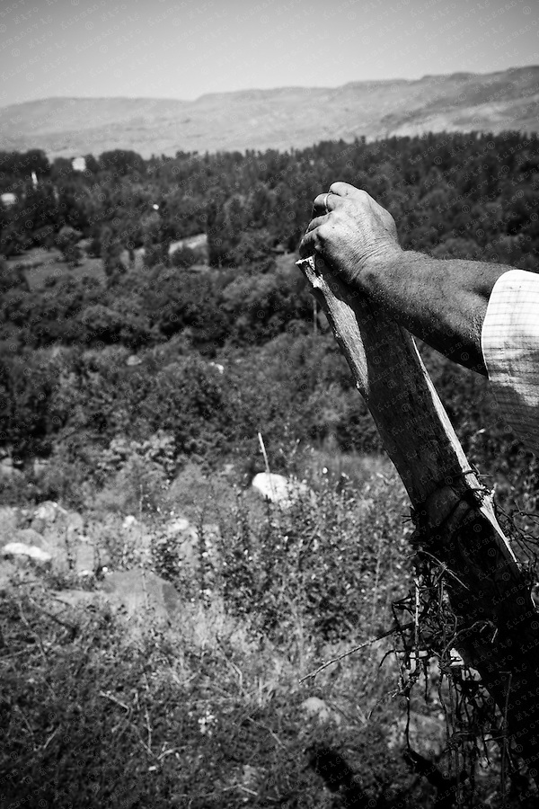 Davit Danielyan stands next to the barbed wire fence as he looks at Turkey's border village of Halikislak, from the Bagaran village in Armenia. Memories of the mass killings of hundreds of thousands of Armenians under the Ottoman Empire run deep between these two villages. To escape from the genociede, the residents of Bagaran, one of the oldest settlements capital of Armenia, crossed the left bank of the Akhuryan River.