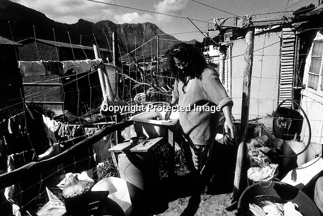 disipov00077.Social Issues. Poverty. Lynette Matthe doing her laundry outside the family shack on September 27, 1998 in Hout Bay outside Cape Town South Africa. She lives with their unemployed husband Kallie and their two children in shack in poor black squatter camp. More and more whites has found it more difficult to get jobs in the new South Africa due to affirmative action laws..©Per-Anders Pettersson/ iAfrika Photos