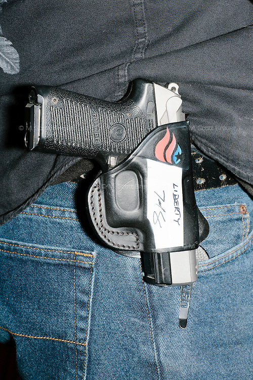 "A pistol in a holster with Ted Cruz's campaign logo and his autograph hangs on the belt of Marc McInnis, of Salem, New Hamsphire, as Texas senator and Republican presidential candidate Ted Cruz speaks at a Second Amendment Rally outside Granite State Indoor Range in Hudson, New Hampshire. Above the autograph, Cruz also wrote ""liberty."""