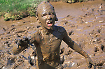 A073NW Monster like child  playing in thick mud with head and body covered by brown mud