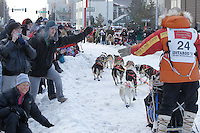 Billy Snodgrass gives a high-five to spectators along Cordova Street in downtown Anchorage, Alaska during the ceremonial start of the 2011 Iditarod