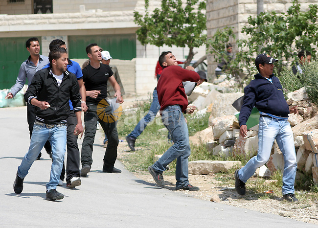 Palestinian protestors throw stons at Israeli soldiers during a demonstration against Israel's controversial separation barrier in the West Bank village of Maasarah, near the biblical town of Bethlehem on April 29, 2011.Israel says the network of steel and concrete walls, fences and barbed wire is needed for security while the Palestinians view it as a land grab that undermines their promised state. Photo by Najeh Hashlamoun