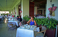Young woman enjoying breakfast at Orchids restaurant at the Halekulani hotel in Waikiki