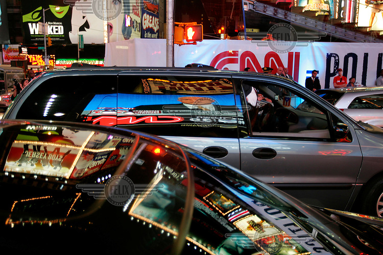 John McCain, Republican candidate for President, is shown on a giant television screen in Times Square making his speech at the Republican National Convention. Car windows reflect the screen and the neon lights of advertising signs.