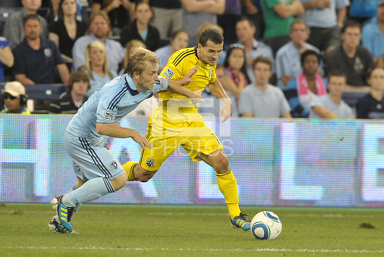 Dilly Duka (yellow) Columbus Crew midfielder moves past Sporting KC defender Seth Sinovic... Sporting Kansas City defeated Columbus Crew 2-1 at LIVESTRONG Sporting Park, Kansas City, Kansas.