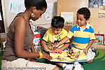 Education Preschool 3-5 year olds female student teacher reading book to two boys horizontal