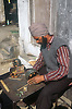 Man working at table in street in Gobindigarh making armatures for electric motors,