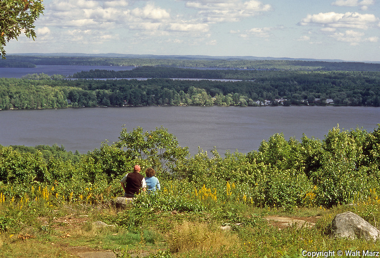 A couple enjoy the vlew from Blueberry Hill, Rome, Maine. <br /> Upper Long Pond in forground; Belgrade Village in center and Great Pond in background.