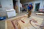 Ekhlas Mohamad cleans a carpet in her home in Mosul, Iraq. The woman participated in a sewing course conducted by RNVDO which has helped her to earn income for her family. The class was supported by the ACT Alliance.