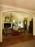 View through an arched doorway to the elegant living room furnished with a pair of Chesterfield sofas and a pair of retro chairs
