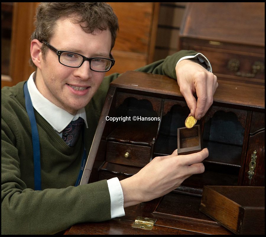 BNPS.co.uk (01202 558833)<br /> Pic: Hansons/BNPS<br /><br />Delighted - Coin expert Edward Rycroft.<br /> <br /> A woman has told of her delight after a 700-year-old gold coin worth £3,000 was found in a secret drawer in a writing desk a relative had left her.<br /> <br /> Amy Clapp, 37, had no idea the 22ct French coin was inside the 20th century bureau and it was only four after she sent the item of furniture off to auctioneers.<br /> <br /> Furniture expert Edward Rycroft discovered it when he examined the bureau at Hansons Auctioneers.<br /> <br /> The coin is a Raymond IV Prince of Orange Franc A Pied coin dating back to 1365.