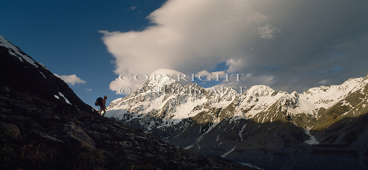 Tramper looking at Mount Cook in Mount Cook National Park. Cloud over summit of the mountain. New Zealand