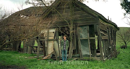 Trent Nelson in front of old, abandoned home.; San Ramon, CA<br />
