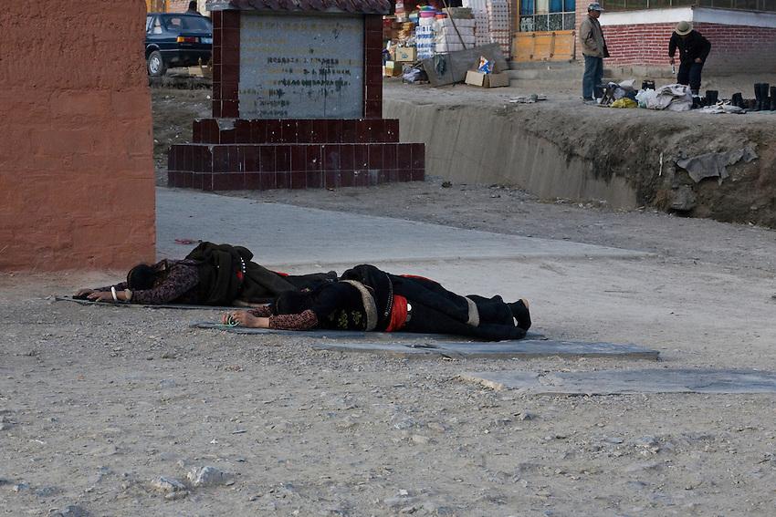 Deux tibétaines effectuent la prostration face à l'allée principale tu monastère de Labrang.