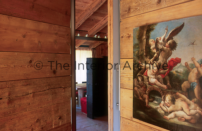 An unframed Renaissance-style painting strikes a note of contrast in the entrance hall of the chalet