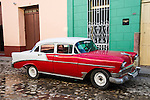 TRINIDAD, CUBA - DECEMBER 28: A vintage car parked on a cobblestone street in Trinidad, Cuba on December 28, 2013.  Prior to 2011, Cuban citizens could only purchase pre-revolution vehicles.