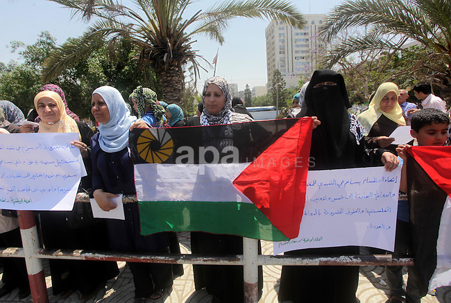 Palestinian women hold banners during a protest against split between Palestinian factions in Gaza city on May 7, 2013. The splitting started on 2006, after Hamas Islamic Movement had won in the legislative elections. Photo by Ashraf Amra