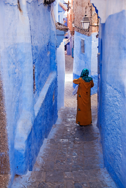 A young woman in an orange gown is descending a narrow passageway in the blue city of Chefchaouen, Morocco