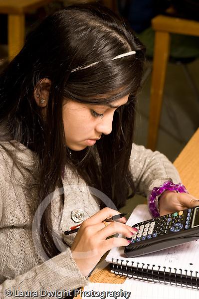 Education High School Mathematics class female student using calculator vertical