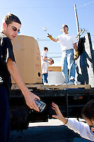 Volunteers from First Street United Methodist Church unload canned goods at the community center the Dwelling Place in uptown New Orleans on November 24, 2005.