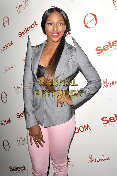 Alexandra Burke.The launch of her 'MUA Lip Enhancing Lipstick and Gloss Collection' at the Rose Club, London, England..11th April 2012.half length grey gray suit jacket blazer shoulder pads pink lipstick jeans denim ponytail hand on hip bra.CAP/MAR.© Martin Harris/Capital Pictures.