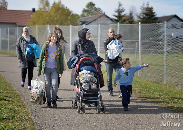 Syrian refugees walk through in Messstetten, Germany. They have applied for asylum in Germany and are awaiting word on the government's decision. Meanwhile, they live in a room in a former army barracks in Messstetten.