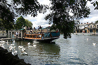 A pleasure boat takes on passengers at the Windsor jetty on the River Thames.