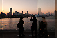 People watch the sunset over the Yokohama, Minato Mirai skyline from the Osanbashi Pier in Yokohama, Kanagawa, Japan Sunday March 25th 2018