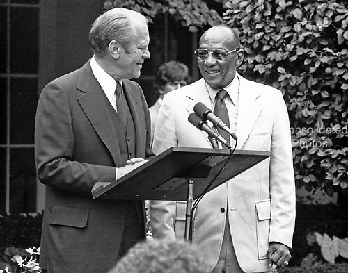 "United States President Gerald R. Ford, left, and Jesse Owens, right, American track and field athlete and four-time Olympic gold medalist in the 1936 games, in the East Garden of the White House in Washington, DC during an event to honor the US stars of the 1976 Olympic Games in Montreal on August 5, 1976.  The President later presented Mr. Owens with a plaque from the US Government and praised him for his athletic accomplishments.<br /> Credit: Benjamin E. ""Gene"" Forte / CNP"