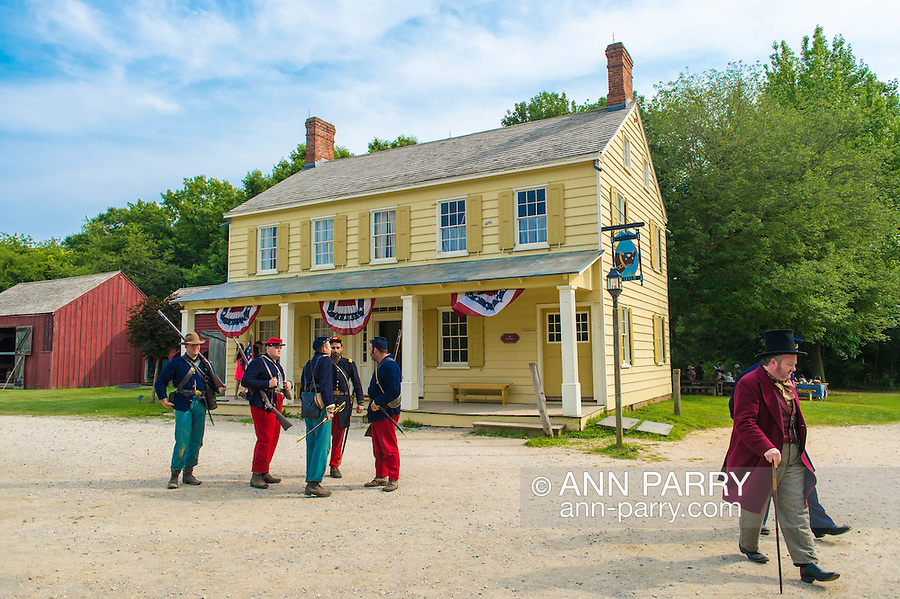 "Old Bethpage, New York, USA. 30th August, 2015. A 19th Century gentleman wearing a top hat, and American Civil War soldiers from the 14th Brooklyn Regiment (14th New York State Militia) AKA The Brooklyn Chasseurs, are portrayed in front of the yellow Noon Inn tavern during the Old Time Music Weekend at the Old Bethpage Village Restoration. During their historical reenactments, members of the non-profit 14th Brooklyn Company E wear reproductions of ""The ""Red Legged Devils"" original Union army uniform."