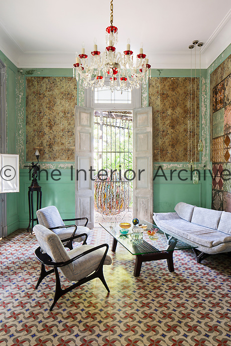 The walls of the living room feature panels of original 1940s wallpaper and the textile wall hanging found during the restoration of the house is of the same period