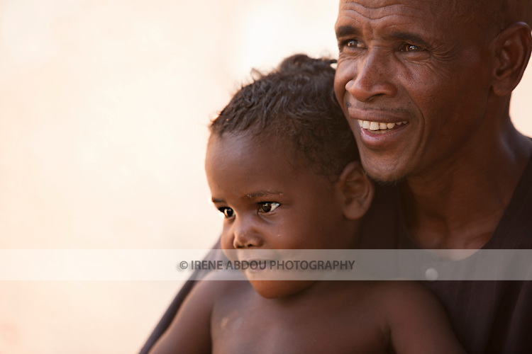 In Djibo in northern Burkina Faso, a Fulani man holds his daughter in his lap.