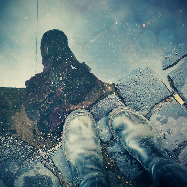 a girl taking a picture reflected in a puddle