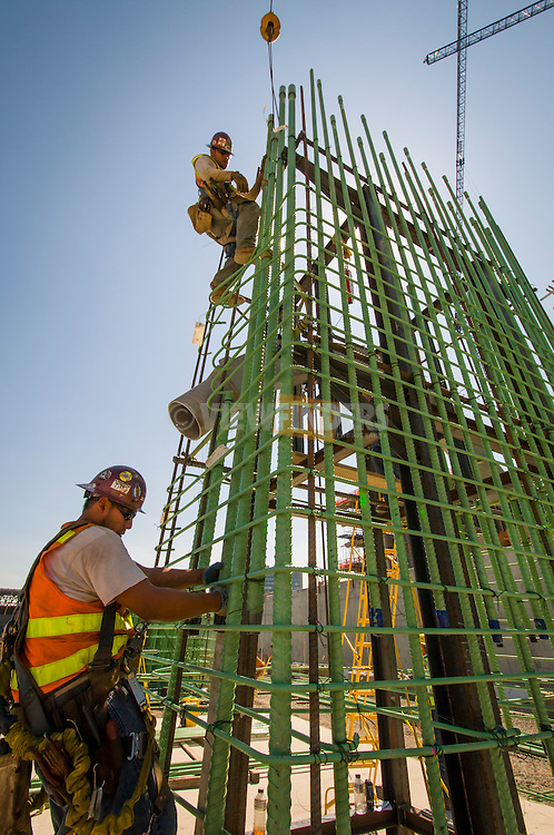 Construction workers climbing a tower of rebar at Trimet's Portland-Milwaukie Light Rail Bridge Project.