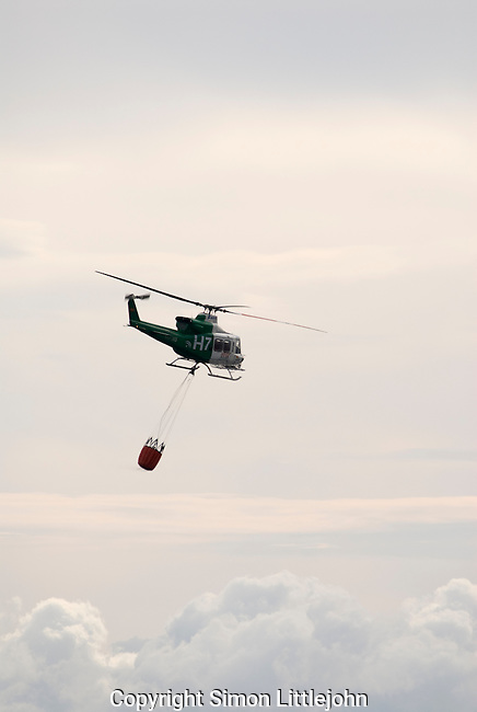 Bell  helicopter with suspended water ballon assisting in fighting forest fire, Los Reales mountain, Estepona, Andalucia, Spain.