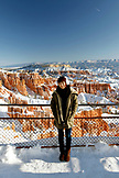 USA, Utah, Bryce Canyon City, Bryce Canyon National Park, portrait of a Korean tourist in front of the Bryce Amphitheater and Hoodoos, Sunset Point