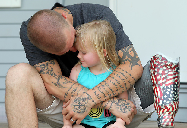 Joel Klobnak, 24, hugs his daughter, Grace, 3, outside his Greenfield home June 8.  He lost his leg and developed PTSD during a tour of Iraq with the Marines in 2006.