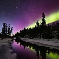 Northern lights reflect in a stream in the Alaska Range mountains, Interior, Alaska.
