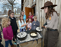 NWA Democrat-Gazette/ANDY SHUPE<br /> Laura Jennings (right), park interpreter at Battlefield State Park in Prairie Grove, smiles as she shows children a batch of biscuits made in a Dutch oven Friday, March 23, 2018, during a Pioneer craft day camp at the park. Campers learned about weaving, sewing, native plants, and other skills used by early settlers as a part of a spring break camp.